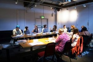 Image shows a scene from a workshop with participants sitting around two tables