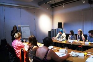 Image shows a scene from a workshop with Trish standing at the front with a flip chart and participants seated around tables in front of her