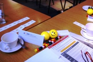 Image shows a scene from a workshop with cup and saucer, workbook and smiley face stress ball